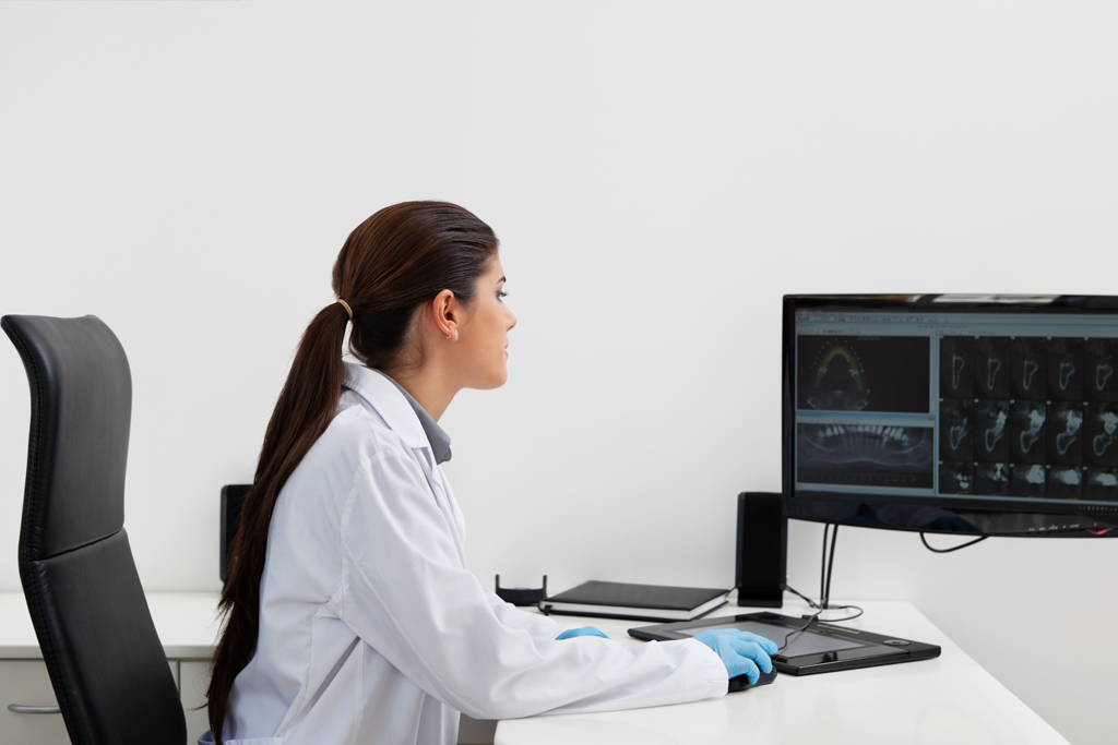 Doctor sitting at desk looking at computer screen